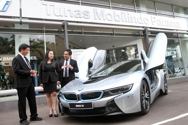 Vice President Corporate Communication BMW Group Indonesia Jodie O'tania (tengah), bersama Head of Sales Channel Development Irhan Farhan (kanan), dan Chief Operating Officer PT Tunas Mobilindo Parama BMW Purwoko Arbutomo, mengamati kendaraan BMW i8, di Jakarta, Selasa (12/12). - JIBI/Endang Muchtar