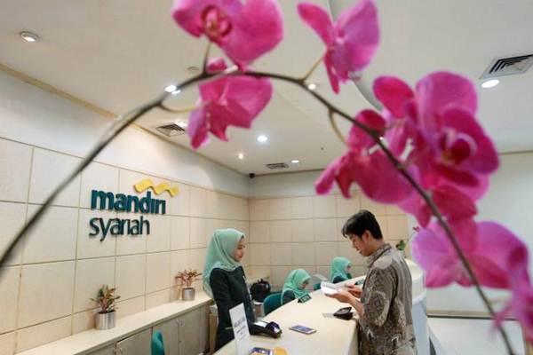 Karyawan melayani nasabah di banking hall PT Bank Syariah Mandiri (BSM) di Jakarta. - JIBI/Dwi Prasetya