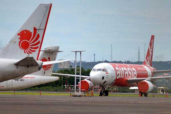 Pesawat AirAsia (kanan) diparkir di landasan pacu Bandara Internasional Ngurah Rai di Bali. - Antara/Wira Suryantala