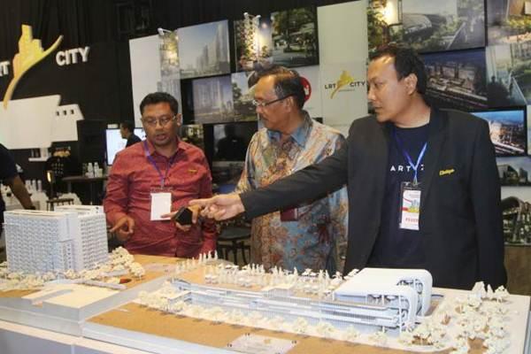 Direktur Operasi PT Adhi Karya Tbk Budi Saddewa Sudiro (tengah), bersama Projects Manager LRT City Gateway Park Ibnu Mahmud Junaidi (kiri), dan Manager Biro Keuangan Muhamad Yusuf , mengamati maket proyek kereta ringan (light rail transit/LRT), di arena Indonesia Properti Expo, Jakarta, Senin (14/8). - JIBI/Endang Muchtar