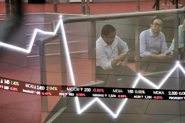 Karyawan beraktivitas di dekat layar Indeks Harga Saham Gabungan (IHSG), di Bursa Efek Indonesia (BEI), Jakarta, Selasa (21/11). - JIBI/Felix Jody Kinarwan