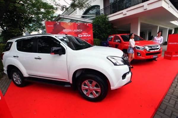 Model berfoto dengan dua mobil segmen sport utility vehicle (SUV) New Isuzu mu-X dan New Isuzu D-Max VGS saat peluncuran di Jakarta, Senin (8/8). Untuk mu-X, dipasarkan dengan harga Rp448 juta untuk 4x4 AT Description: JIBI/Bisnis - Dwi Prasetya