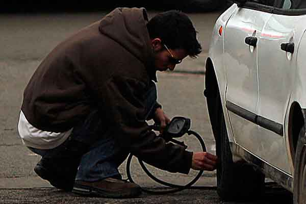 Mengecek tekanan udara pada ban mobil.  - Reuters