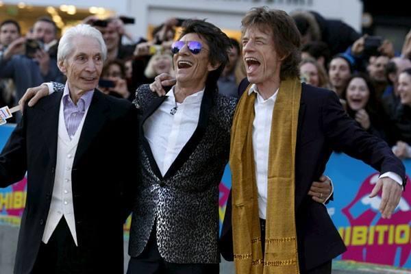 """Anggota Rolling Stones (ki-ka) Charlie Watts, Ronnie Wood dan Mick Jagger menunggu Keith Richards saat mereka tiba di malam pembukaan gala """"Exhibitionism"""" di Saatchi Gallery di London, Inggris Raya, pada foto 4 April 2016 - Reuters"""