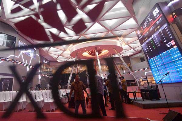 Karyawan dan pelaku usaha berada di dekat monitor pergerakan Indeks Harga Saham Gabungan (IHSG) di Bursa Efek Indonesia, Jakarta, Jumat (16/3/2018). - ANTARA/Sigid Kurniawan