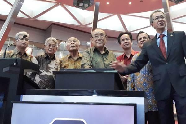 Direktur Utama PT Emdeki Utama Tbk Hiskak Secakusuma (tengah) bersama manajemen dan Direktur PT Bursa Efek Indonesia (BEI) Alpino Kianjaya  (kanan) melakukan pemencetan tombol, sebagai tanda pencatatan perdana saham perseroan, di BEI , Jakarta, Senin (25/9). - JIBI/Endang Muchtar