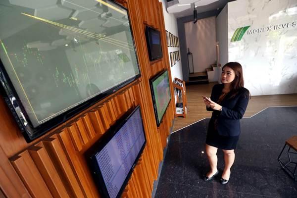 Karyawati mengamati pergerakan harga komoditas melalui ponsel dan layar monitor di kantor PT Monex Investindo Futures (Monex) Bandung, Jawa Barat, Jumat (13/4/2018). - JIBI/Rachman