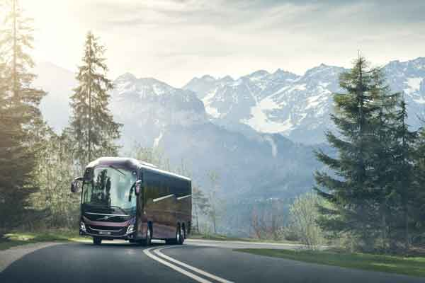 Bus Volvo sedang melintasi jalan di pegunungan.  - Volvo