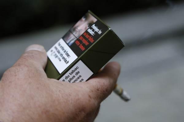 Seorang pria memegang kemasan rokok di Paris (25/9/2014). - Istimewa