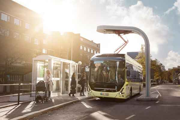 Bus bertenaga listrik tengah mengisi daya di dekat sebuah halte.  - Volvo