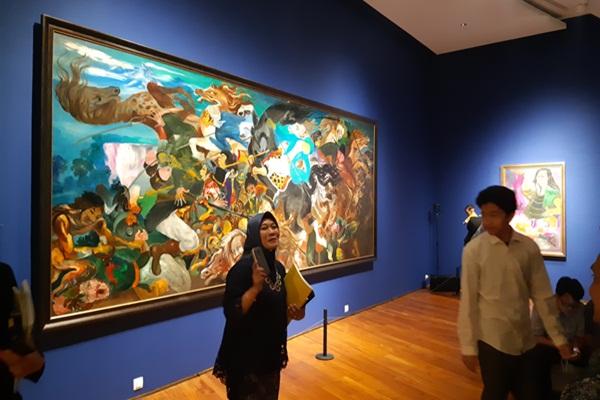Seorang perempuan berdiri di depan salah satu lukisan Hendra Gunawan, Sabtu (4/8/2018). - Bisnis/Rayfur Mudassir
