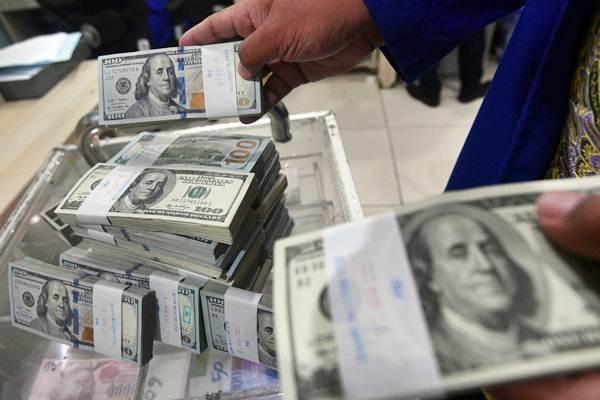 Petugas menata tumpukan uang dolar AS/ANTARA FOTO - Sigid Kurniawan