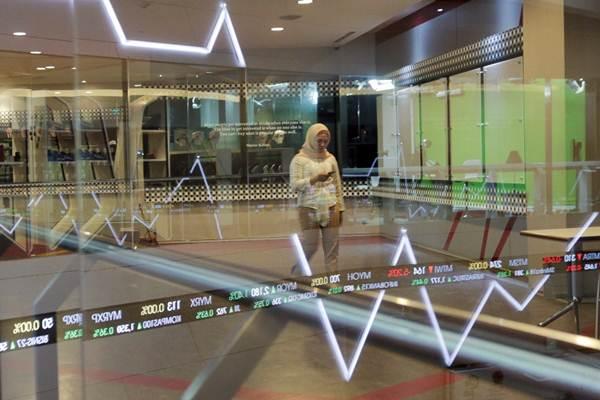 Karyawan beraktivitas di dekat papan pergerakan Indeks Harga Saham Gabungan (IHSG) di Bursa Efek Indonesia, Jakarta, Senin (8/1). - JIBI/Felix Jody Kinarwan
