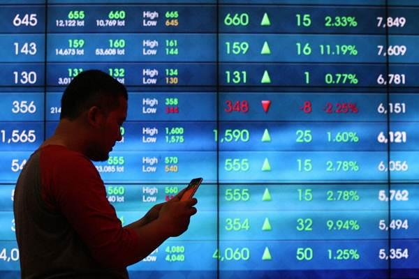 Pengunjung beraktivitas di dekat papan elektronik yang menampilkan perdagangan harga saham, di Jakarta, Senin (19/2/2018). - JIBI/Dedi Gunawan