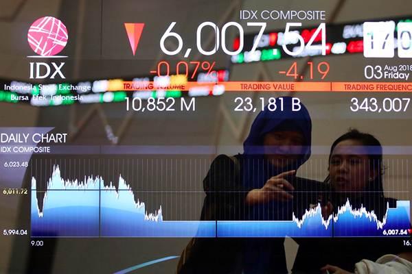 Karyawan melakukan swafoto di dekat papan elektronik yang menampilkan pergerakan Indeks Harga Saham Gabungan (IHSG) di Bursa Efek Indonesia, Jakarta, Jumat (3/8/2018). - JIBI/Abdullah Azzam
