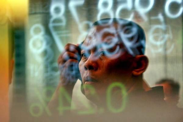 Karyawan melintas di dekat layar pergerakan Indeks Harga Saham Gabungan (IHSG) di Bursa Efek Indonesia, Jakarta, Kamis (23/8/2018). - JIBI/Nurul Hidayat