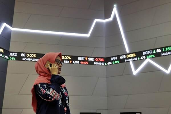 Pengunjung beraktivitas di dekat papan pergerakan Indeks Harga Saham Gabungan (IHSG), di Jakarta, Jumat (26/1/2018). - JIBI/Felix Jody Kinarwan