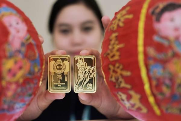 Karyawati memperlihatkan emas batangan 88 gram bergambar Shio Anjing Tanah milik PT Aneka Tambang Tbk (Antam), di Jakarta, Kamis (18/1). - JIBI/Felix Jody Kinarwan