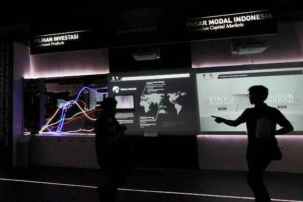 Siluet pengunjung mengamati layar informasi IHSG, di gedung Bursa Efek Indonesia Jakarta, Senin (17/9/2018). - JIBI/Dwi Prasetya