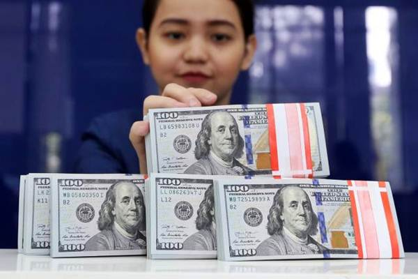 Karyawan memperlihatkan mata uang dolar AS di salah satu bank di Jakarta. - JIIBI/Abdullah Azzam