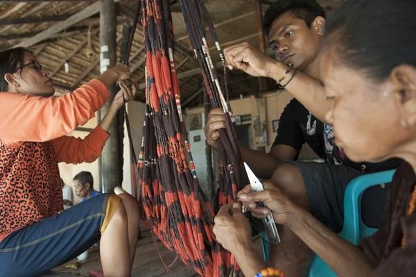 Sejumlah warga mengerjakan pembuatan motif benang untuk tenun ikat khas Sumba di Desa Prailiu, Sumba Timur, Sabtu (24/6). Kerajinan kain tenun dengan pewarna alami tersebut banyak dikembangkan warga sebagai bisnis sampingan bidang pariwisata, selain penghasilan utama mereka di bidang pertanian dan peternakan. ANTARA FOTO - Nyoman Budhiana