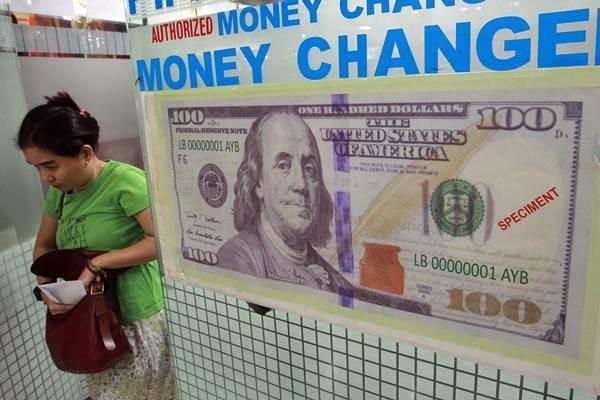 Pelanggan keluar dari gerai penukaran uang asing di Jakarta. - JIBI/Dwi Prasetya