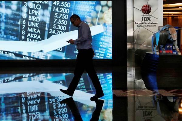 Karyawan berjalan melintasi layar informasi Indeks harga saham gabungan (IHSG) di gedung Bursa Efek Indonesia, Jakarta, Kamis (6/9/2018). - Reuters/Willy Kurniawan