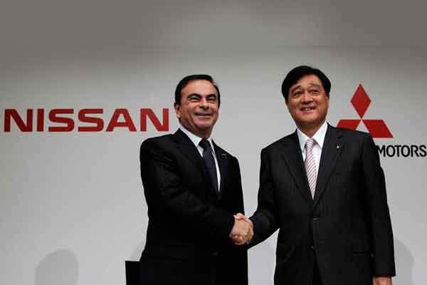 Chief Executive Nissan Motor Carlos Ghosn berjabat tangan dengan President Mitsubishi Motors Corp. Osamu Masuko di akhir sebuah konferensi pers mereka di Tokyo. /Reuters