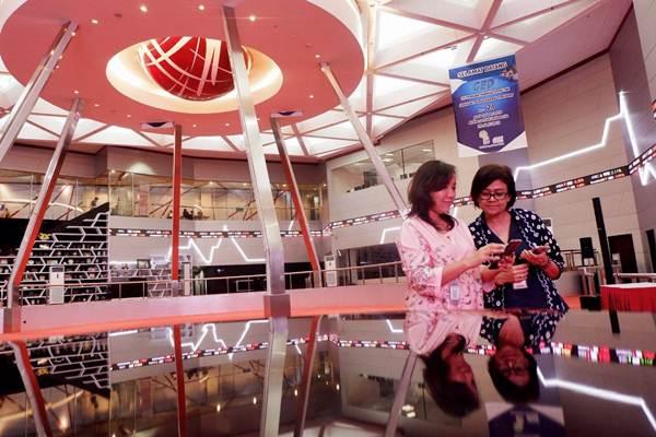 Karyawati berkomunikasi di dekat monitor pergerakan Indeks Harga Saham Gabungan (IHSG) di Bursa Efek Indonesia, Jakarta, Selasa (3/7/2018). - JIBI/Nurul Hidayat