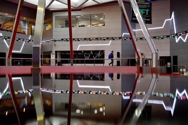 Karyawan melintas di bawah layar monitor pergerakan Indeks Harga Saham Gabungan (IHSG) di Bursa Efek Indonesia (BEI), Jakarta, Kamis (13/9/2018). - ANTARA/Sigid Kurniawan