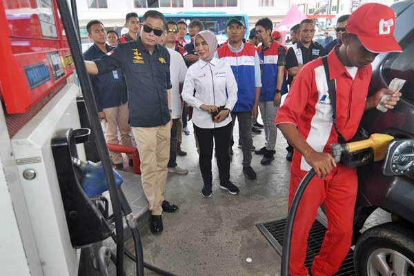 Menteri ESDM Ignasius Jonan (kiri) bersama Dirut Pertamina Nicke Widyawati (kedua kiri) meninjau pengisian bahan bakar minyak (BBM) di salah satu SPBU saat kunjungan kerja di Palu, Sulawesi Tengah, Jumat (19/10/2018). - ANTARA/Mohamad Hamzah