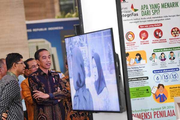 Presiden Joko Widodo (kanan) didampingi Wakil Ketua KPK Laode M Syarif (kiri) mengamati informasi di stan pameran anti korupsi ketika menghadiri peringatan Hari Anti Korupsi Dunia (Hakordia) 2018 di Jakarta, Selasa (4/12/2018). - ANTARA/Wahyu Putro A