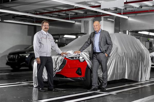 Peter Kssler, Anggota Dewan Manajemen untuk Produksi dan Logistik di AUDI AG dan Ketua Dewan Direksi Audi Brussels (kanan), menyingkap sedikit model Audi e-tron pertama dari seri produksi. Dia ditemani oleh Patrick Danau, Managing Director Audi Brussels. - AUDI