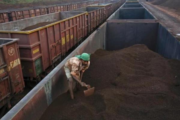 Seorang pekerja sedang meratakan bijih besi di atas kereta cargo di stasiun kereta Chitradurga, di Karnataka, India (9/11/2012)/Reuters/Danish Siddiqui