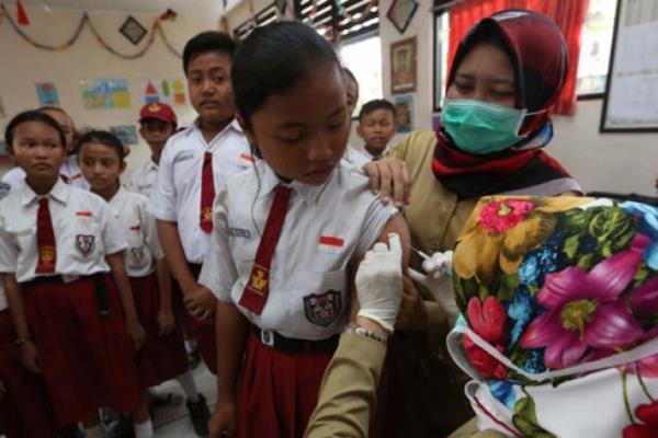 Petugas medis memberikan imunisasi difteri kepada murid Sekolah Dasar (SD). - Antara