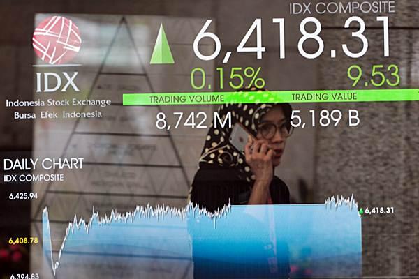 Karyawan melintas di dekat papan penunjuk pergerakan indeks harga saham gabungan (IHSG) di Jakarta, Rabu (16/1/2019). - Bisnis/Felix Jody Kinarwan