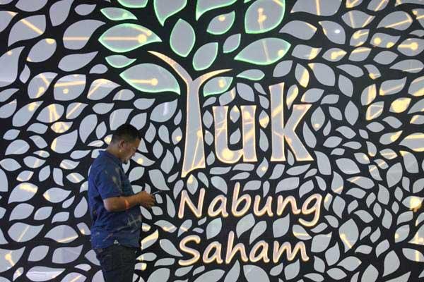 Pengunjung beraktivitas di dekat tulisan Yuk Nabung Saham, di Jakarta, Kamis (3/1/2019). - Bisnis/Dedi Gunawan