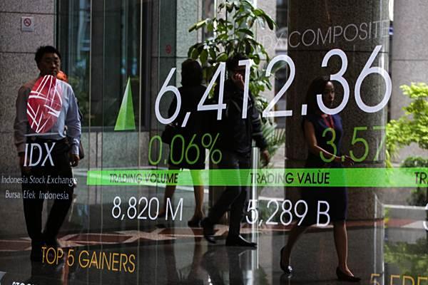 Karyawan melintas di dekat papan penunjuk pergerakan indeks harga saham gabungan (IHSG) di Jakarta - Bisnis/Felix Jody Kinarwan