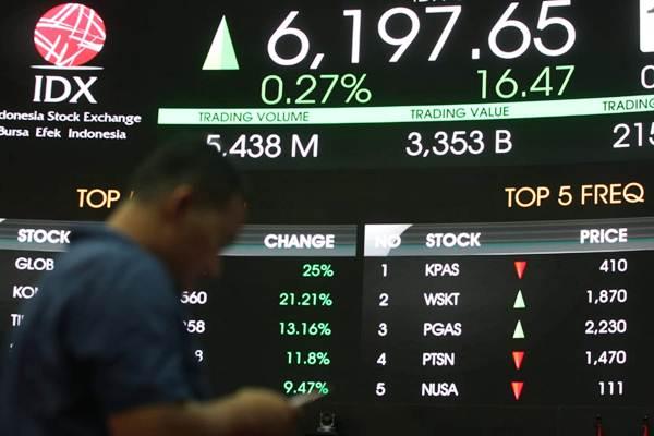 Pengunjung beraktivitas di dekat papan elektronik yang menampilkan perdagangan harga saham, di Jakarta, Kamis (3/1/2019). - Bisnis/Dedi Gunawan