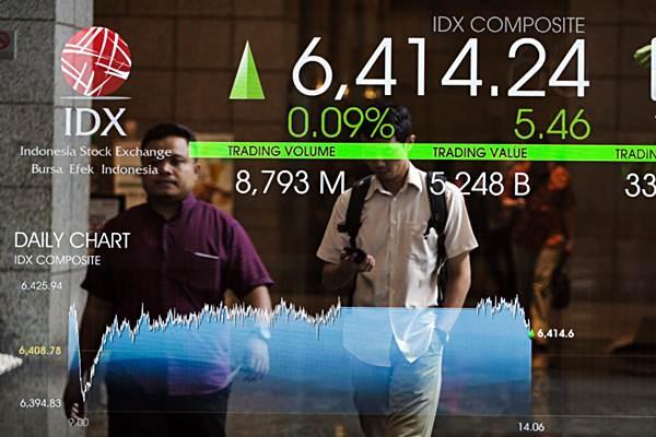 Karyawan melintas di dekat papan penunjuk pergerakan indeks harga saham gabungan (IHSG) di Jakarta, Rabu (16/1/2019). - Bisnis - Felix Jody Kinarwan