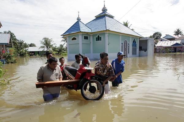 Warga mengevakuasi sepeda motor saat banjir di kompleks perumahan Sawah Lebar Baru, Bengkulu, Kamis (13/12/2018). - ANTARA/David Muharmansyah