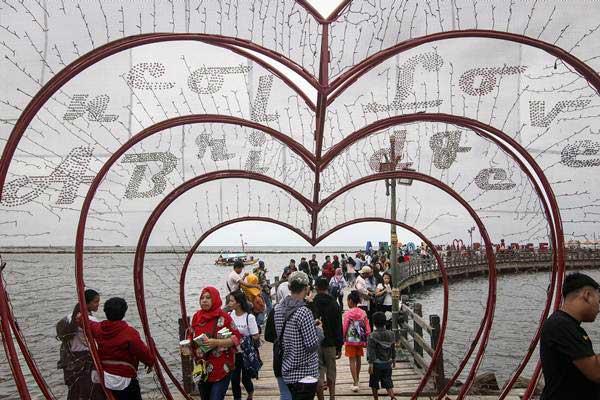 Pengunjung memadati jembatan cinta di Pantai Ancol, Jakarta, Selasa (1/1/2019). - ANTARA FOTO/Dhemas Reviyanto