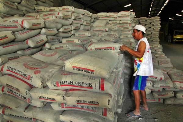 Pekerja membongkar tumpukan karung Semen Gresik, di sebuah gudang distributor PT Semen Indonesia (Persero) Tbk, di Banjarmasin, Kalimantan Selatan, Rabu (12/12/2018). - Bisnis - Wahyu Darmawan