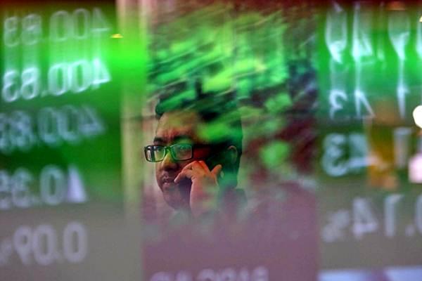 Karyawan melintas di dekat monitor Indeks Harga Saham Gabungan (IHSG) di Bursa Efek Indonesia, Jakarta, Selasa (16/10/2018). - Bisnis/Nurul Hidayat