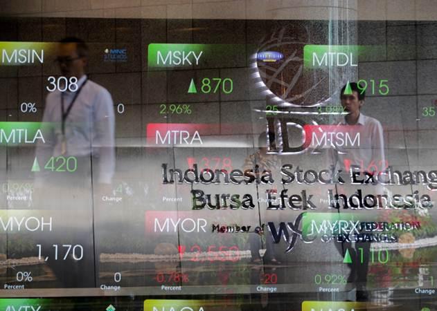 Karyawan melintas di dekat papan pergerakan Indeks Harga Saham Gabungan (IHSG) di Jakarta, Rabu (23/1/2019). - Bisnis/Felix Jody Kinarwan
