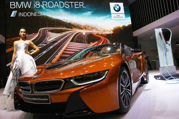 Model berfoto di samping mobil listrik First-Ever BMW i8 Roadster yang diluncurkan pada pameran otomotif Gaikindo Indonesia International Auto Show (GIIAS) ke- 26 di Indonesia Convention Exhibition (ICE) Serpong, Tangerang, Banten, Kamis (2/8/2018). - ANTARA/Muhammad Iqbal