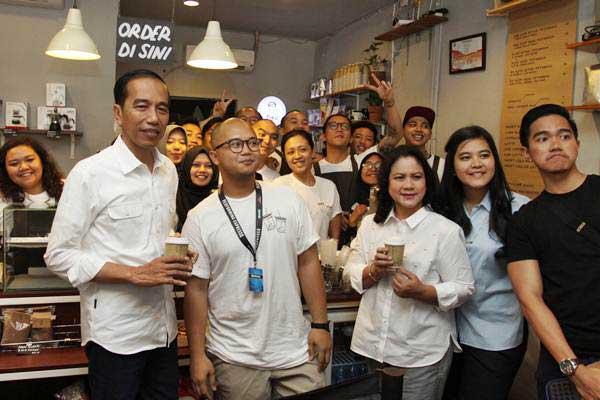 Presiden Joko Widodo (kiri), Ibu Negara Iriana (ketiga kanan) dan dua anak Kaesang Pangarep (kanan) dan Kahiyang Ayu (kedua kanan) didampingi pemilik Tuku Kopi Andanu Prasetyo (kedua kiri) berfoto bersama saat minum kopi di Tuku Kopi, Jakarta, Minggu (2/7). - ANTARA/Reno Esnir