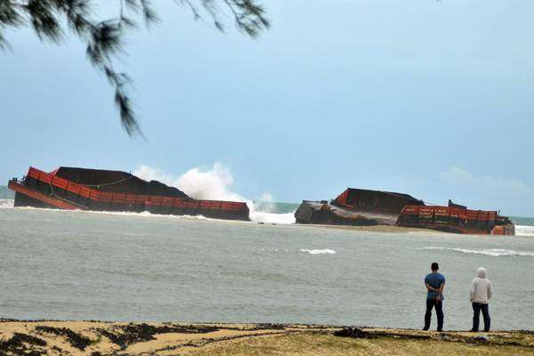 Warga mengamati kapal tongkang batu bara yang kandas dan patah menjadi dua akibat diterjang gelombang besar di perairan pantai Ujung Kareng, Lhoknga, Aceh Besar, Aceh, Senin (30/7/2018). - ANTARA/Ampelsa