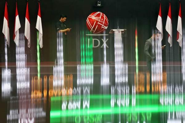 Karyawan berkomunikasi di dekat monitor informasi Indeks Harga Saham Gabungan (IHSG) di Bursa Efek Indonesia, Jakarta, Jumat (11/1/2019). - Bisnis/Nurul Hidayat