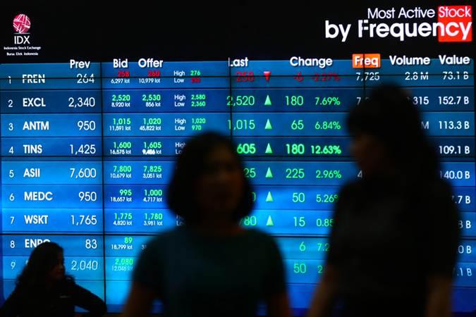 Karyawan melintas di dekat papan elektronik yang menampilkan pergerakan Indeks Harga Saham Gabungan (IHSG) di Bursa Efek Indonesia, Jakarta, Senin (18/2/2019). - Bisnis/Abdullah Azzam